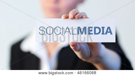 Businesswoman holding a label with social media written on it with focus on the hand