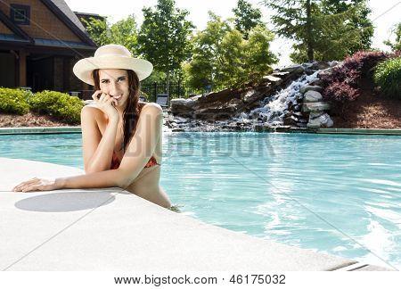 Mujer con sombrero para el sol en la piscina