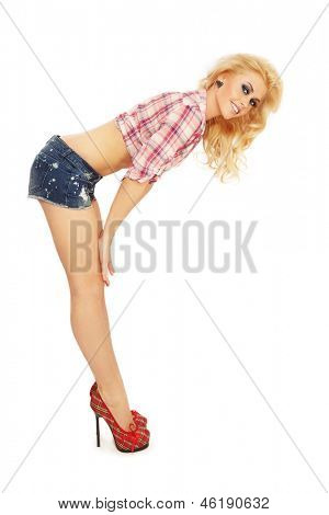 Young beautiful sexy smiling blond girl in casual outfit and stilettos on white background