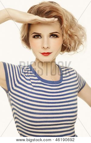 Young beautiful girl in striped sailor top looking upwards, over white background
