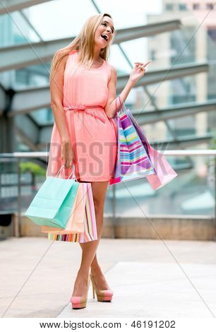 Happy female shopper holding bags and smiling