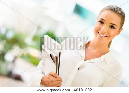 Successful business woman at the office holding documents