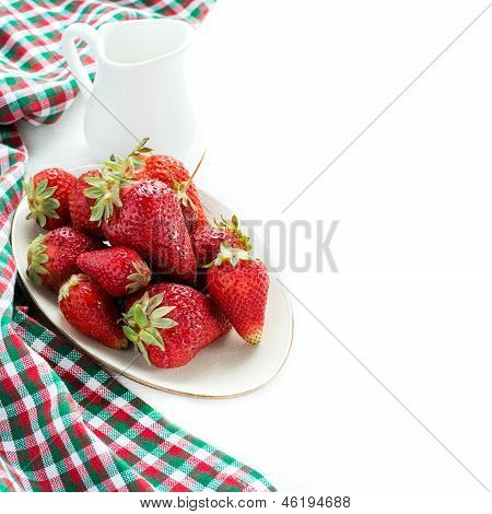 Strawberries on plate and milk over white background