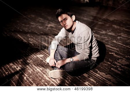 A young brunet man sitting on a wooden floor