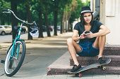 image of skate board  - Happy skateboarder sitting on stairs - JPG