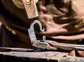 image of blacksmith shop  - A blacksmith is working a piece of iron - JPG