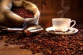 stock photo of coffee-cup  - Coffee cup with burlap sack of roasted beans on rustic table - JPG