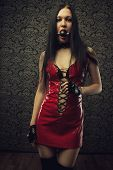 image of masochism  - Pretty girl in red latex dress with mouth gag stands in an empty room - JPG