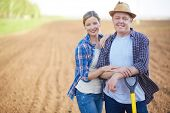 stock photo of plowed field  - Image of two happy farmers on background of plowed field - JPG