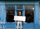 Man standing with a blank sign by a store