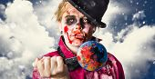 stock photo of gruesome  - Environmental concept of a zombie stabbing a globe of the world with blood stains when killing the planet with global pollution and destruction - JPG