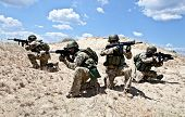 stock photo of assault-rifle  - Squad of soldiers in the desert during the military operation - JPG