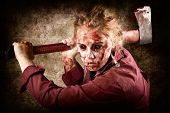 image of gory  - Frightful portrait of a grunge zombie holding rusty old axe when chopping up Halloween victims of horror - JPG