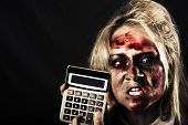 picture of undead  - Mad undead business woman having financial difficulty pressing button on a recession calculator - JPG