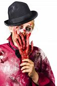 foto of inhumane  - Creepy isolated portrait of a shocked female zombie covering mouth with severed human hand - JPG