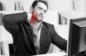 foto of red-necked  - Casual businessman sitting in a desk with pain in his neck black and white red dot around painful area - JPG