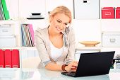stock photo of telemarketing  - Portrait of smiling young woman working at the office on a laptop - JPG