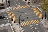 stock photo of traffic signal  - A high angle view of an almost empty street intersection with yellow cross walk markings traffic signal lights and curb cuts in San Jose - JPG