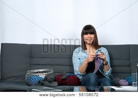 Young Woman Knits On The Couch