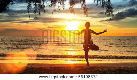 Young yoga woman silhouette. Exercises on the beach during a beautiful sunset.