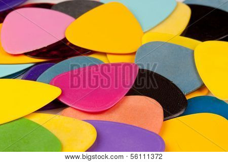 a stack of various color guitar picks on white
