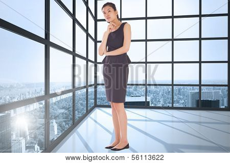 Thoughtful businesswoman against room with large windows showing city