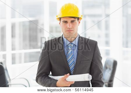 Serious architect holding blueprints looking at camera in the office