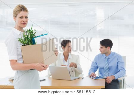 Portrait of a young businesswoman leaving office with her belongings and colleagues in background