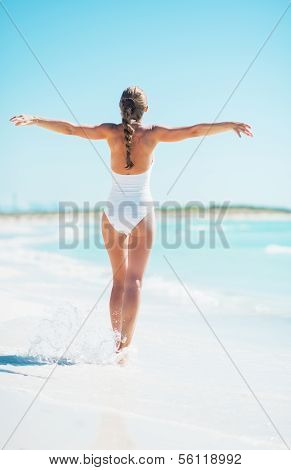 Full Length Portrait Of Young Woman Rejoicing On Beach. Rear Vie