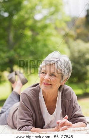 Thoughtful senior woman looking away while lying at the park