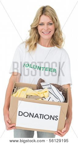 Portrait of a smiling young woman with clothes donation over white background