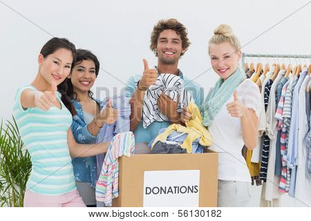 Group of young people with clothes donation gesturing thumbs up