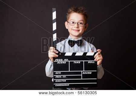Little boy holding clapper board in hands.