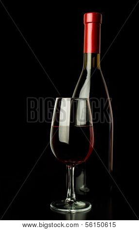 Red Wine Glass And A Wine Bottle Over Black