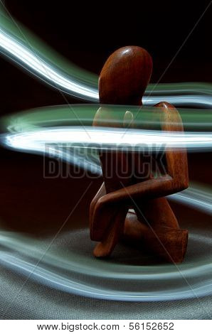 Wooden Figure Surrounded By Light