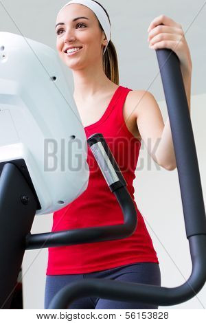 Happy Young Woman  With Elliptic Machine In The Gym
