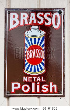NR SOUTHAMPTON,UK - 25 June 2013: Old style tin advertising board for Brasso Metal Polish displayed on painted wood background. On 25 June 2013 Near Southampton UK