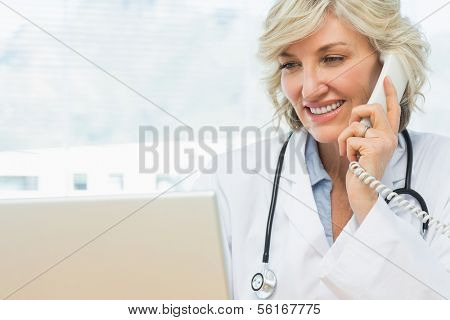 Portrait of a smiling female doctor using laptop and phone in the medical office