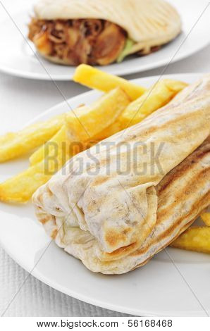 closeup of a durum kebab with fries and a doner kebab in the background on a set table