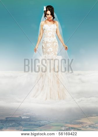 Bride In Wedding White Dress Standing On A Cloud And Looking To The Ground