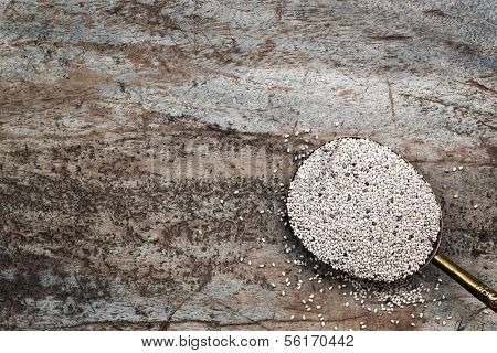 Spoonful of white chia seeds, over grunge timber background.