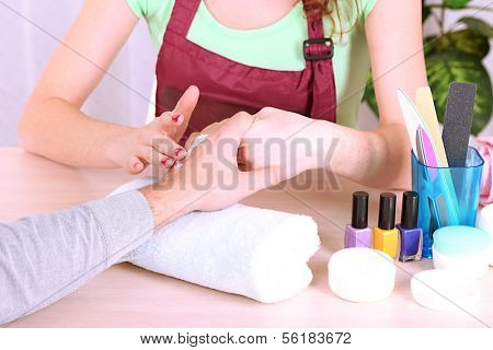 Girl manicurist doing manicure for man in beauty salon