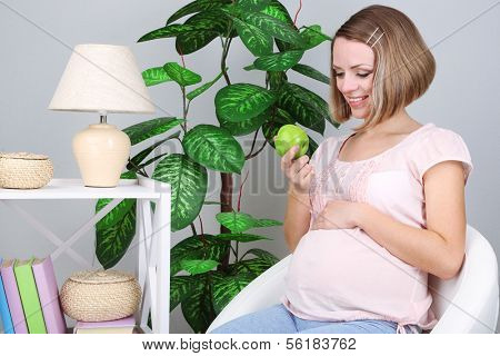 Young regnant woman sitting on armchair and holding apple at home