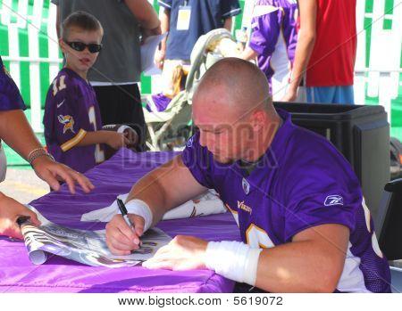 Minnesota Vikings Linebacker Heath Farwell assina autógrafos.