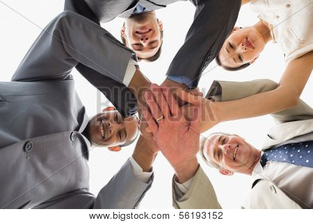 Business team looking down at the camera with hands together in the office