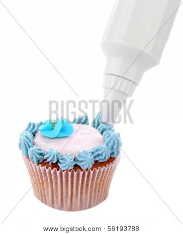 Confectioner decorating tasty cupcake with butter cream, isolated on white