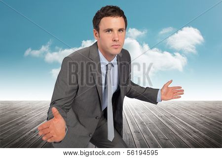 Businessman posing with hands out against cloudy sky background