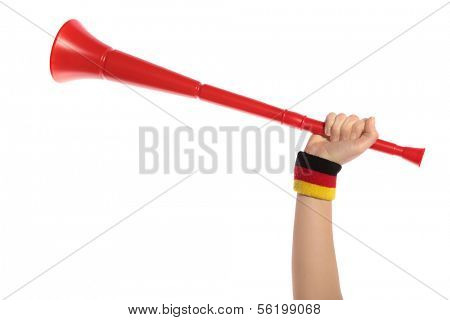 A human hand with a sweatband in German colors holding a vuvuzela, the traditional trumpet of south african supporters