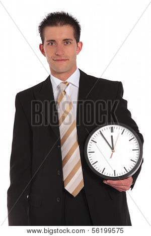A handsome businessman holding a clock that shows the eleventh hour. All on white background.