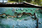 stock photo of dumpster  - A detailed close up macro photograph of cracked and peeling painted dumpster - JPG